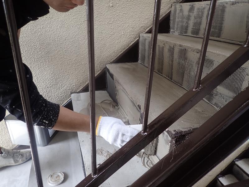 水たまりのできる階段廊下の改修工事 タキステップ6Wと長尺シート防水工事 RAステップ6W接着剤塗布